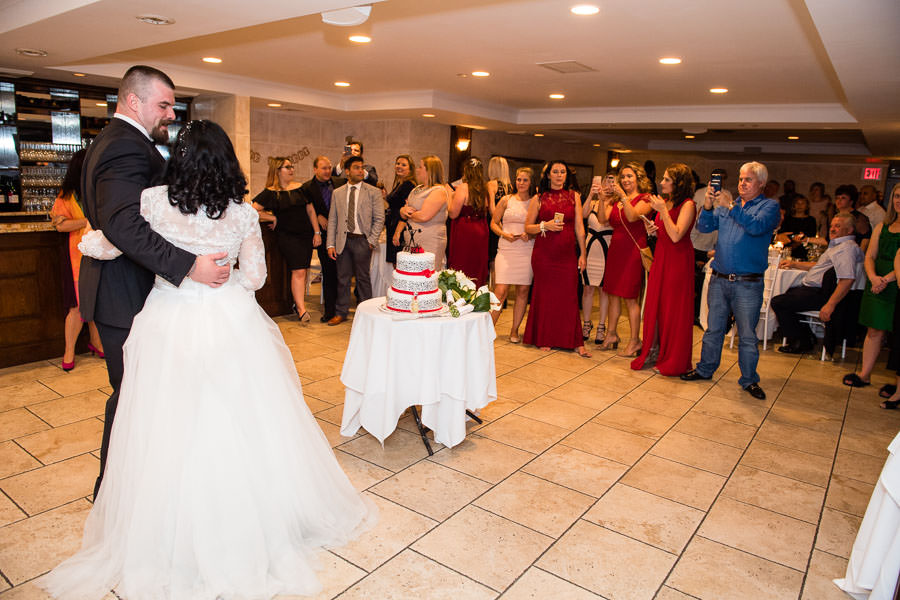 bride and groom pose for photos for their guests in front of the wedding cake