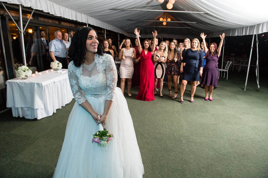 bride throws bouquet at wedding in giando on the water