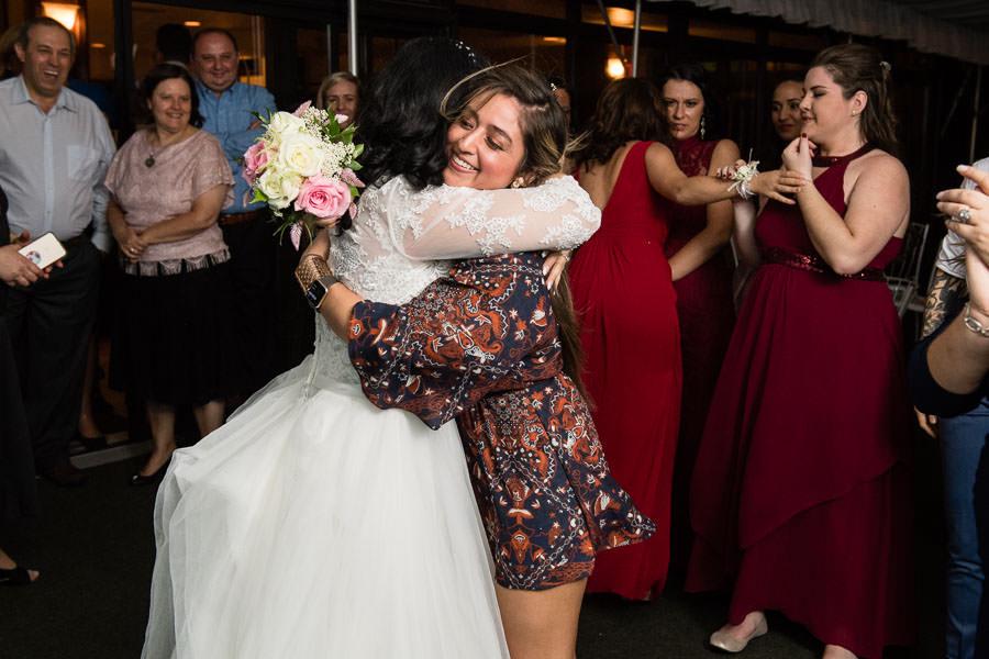 bride hugs girl that caught wedding bouquet