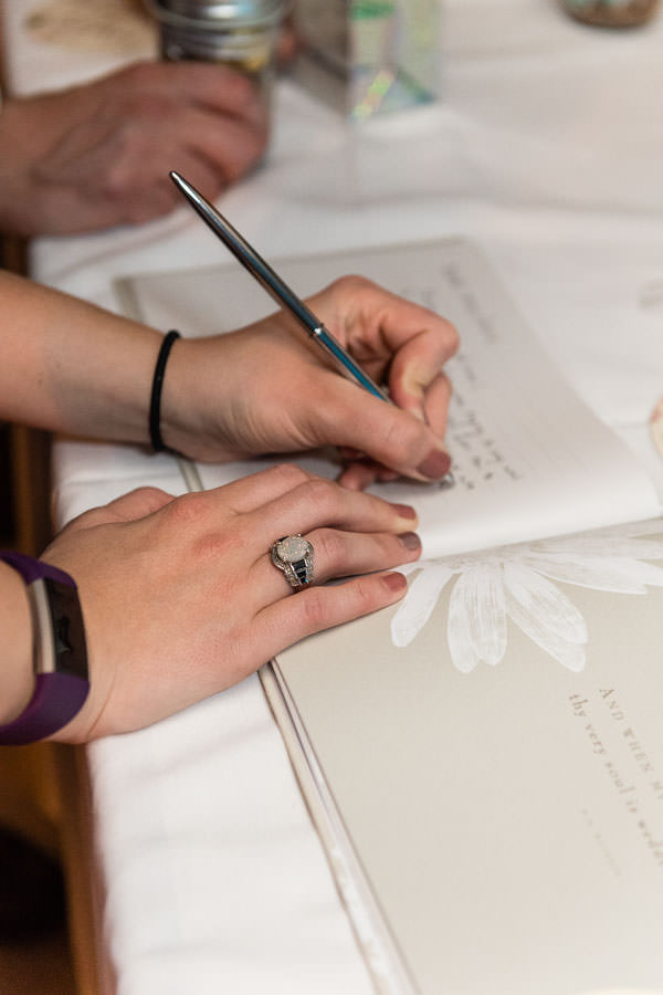 close up of guests signing wedding guest book