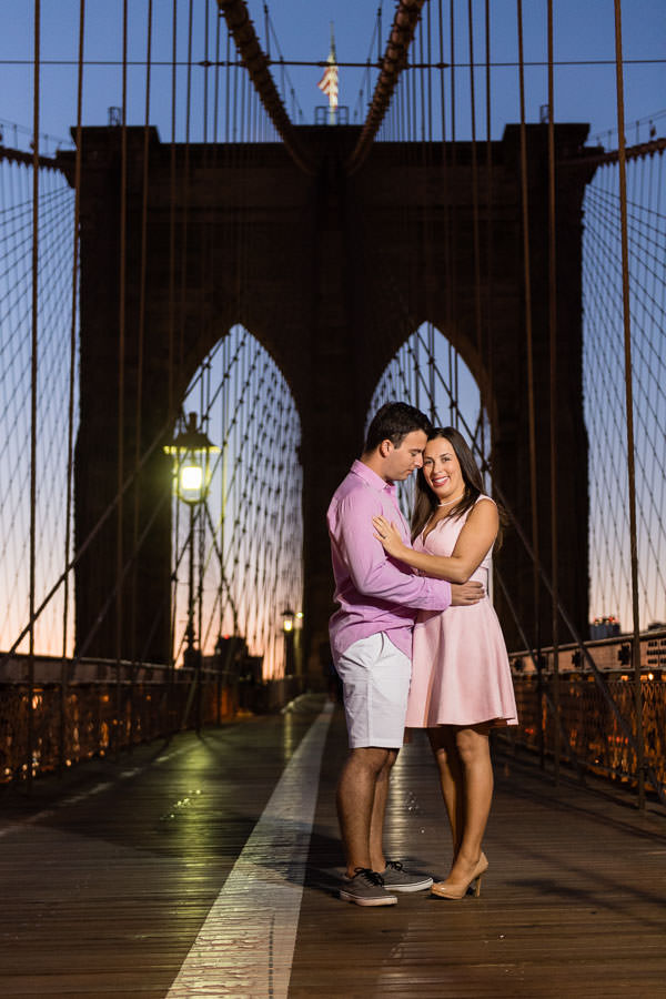 guy in pink shirt and shorts stand with his fiance in pink dress for engagement session during sunrise on brooklyn bridge in new york city