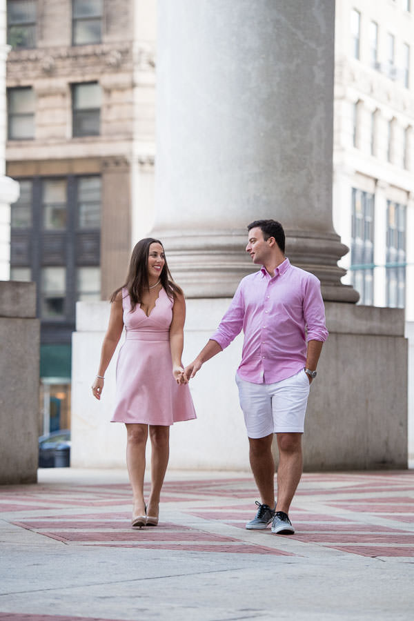 guy and girl hold hands as they walk by city hall in downtown manhattan nyc