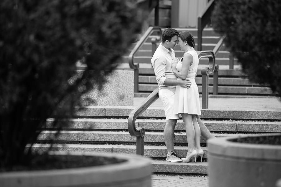 guy and girl hold each other and kiss on the steps for their engagement session next to brooklyn bridge