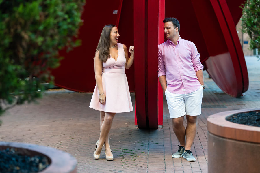 guy and girl pose next to red sculpture in downtown manhattan for engagement session