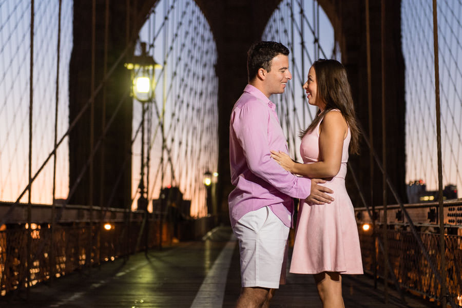 couple holds each other during sunrise on brooklyn bridge during engagement session