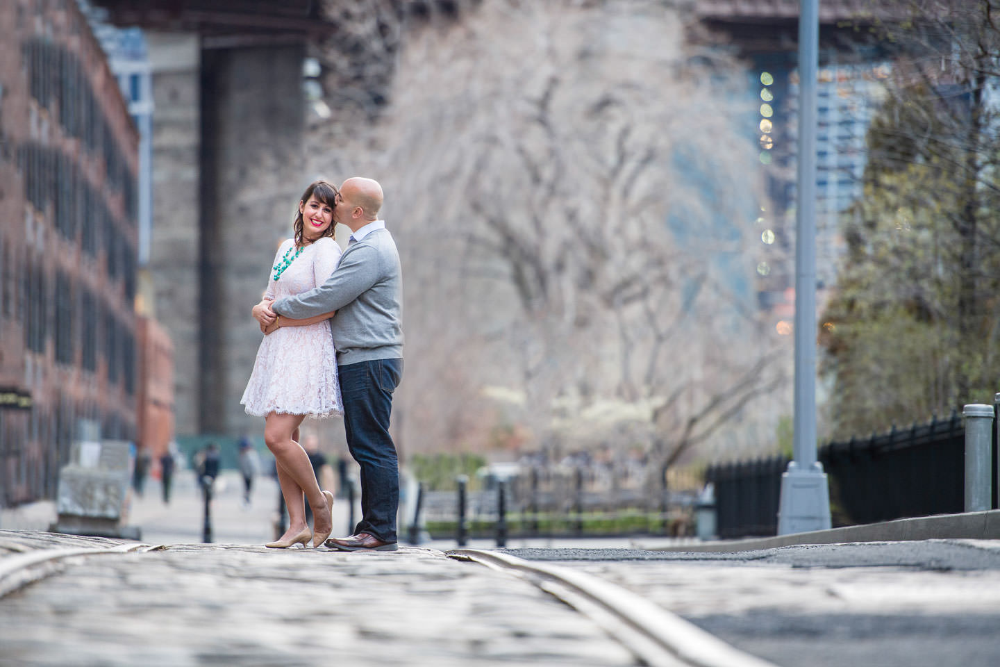 couple engagement session in dumbo during the spring standing on cobblestone