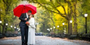 groom holding red umbrella over his bride as they stand in central park with beautiful yellow fall foliage