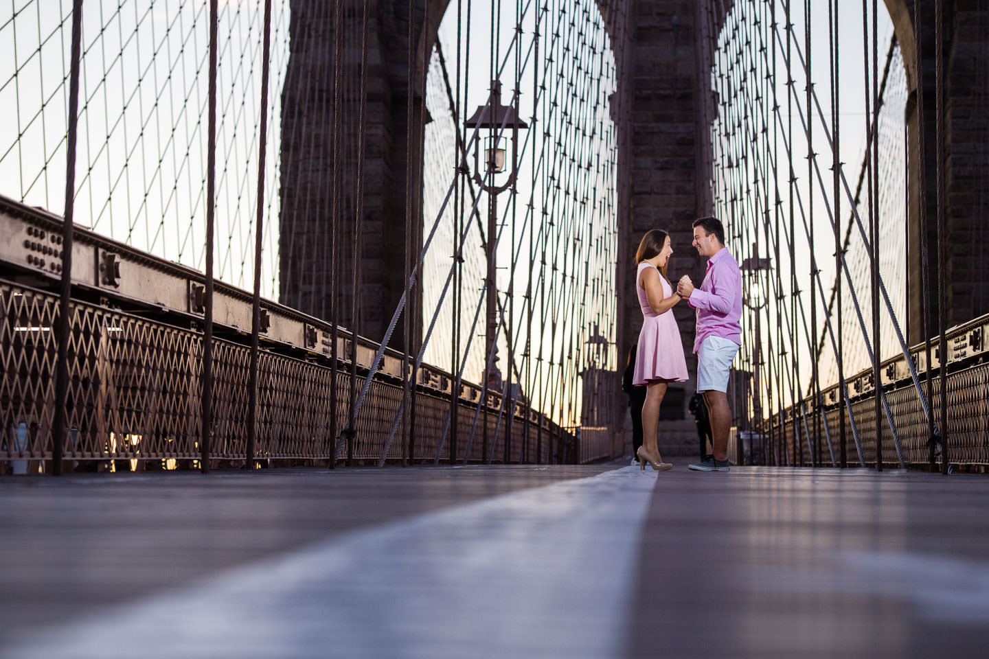 guy and girl stand alone on brooklyn bridge during sunrise for their engagement session