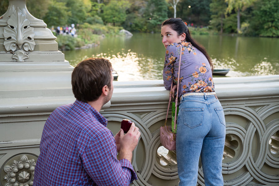 girl is shocked when her boyfriend proposes to her on bow bridge in Central Park