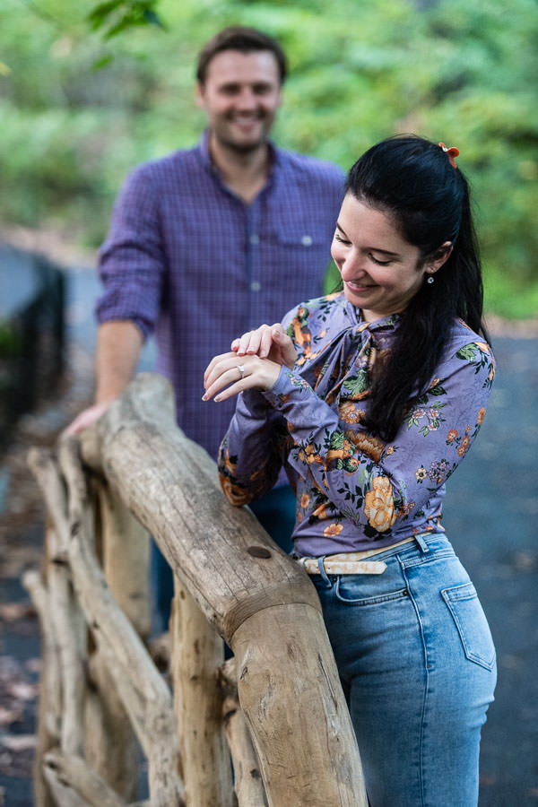 girl looks at her engagement ring while her fiance stands in the background looking at her on wooden bridge in central park