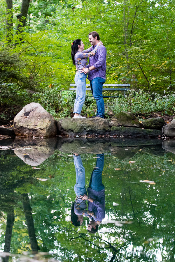 man and girl stand holding each other next to lake with their reflection in the lake during engagement session in central park