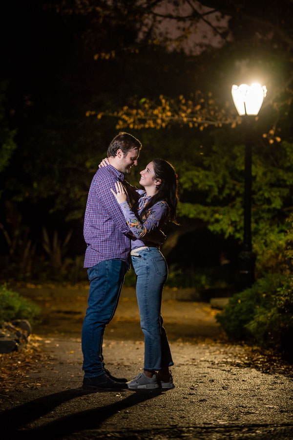 night time photo with street lamp of engaged couple on walking path in central park