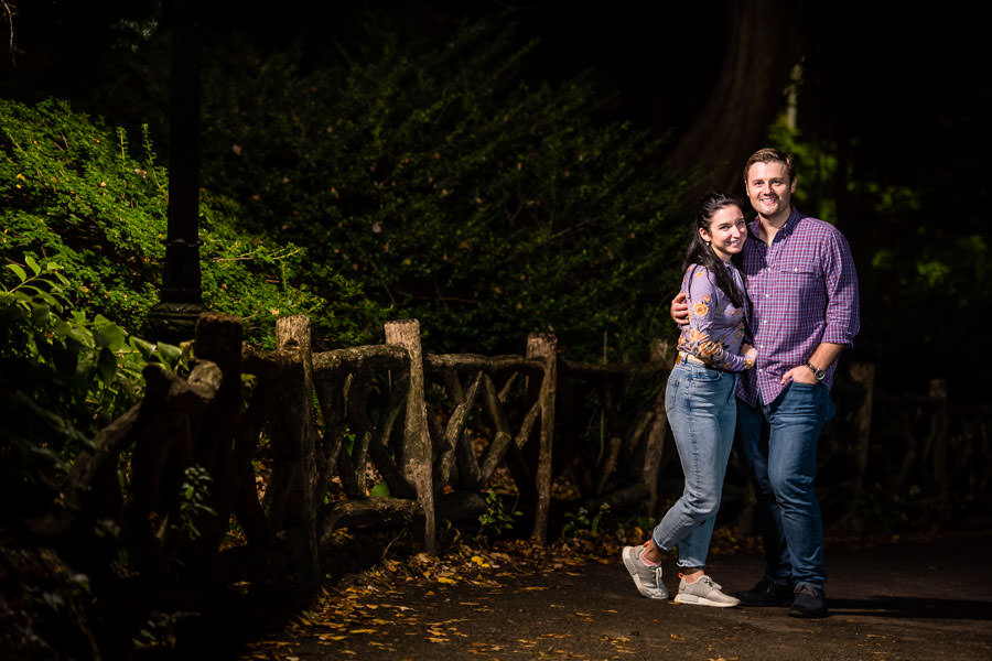 night time engagement session in central park with couple standing next to wooden fence