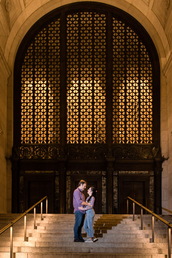 engagement session at museum of natural history with couple standing on the steps and holding each other at night