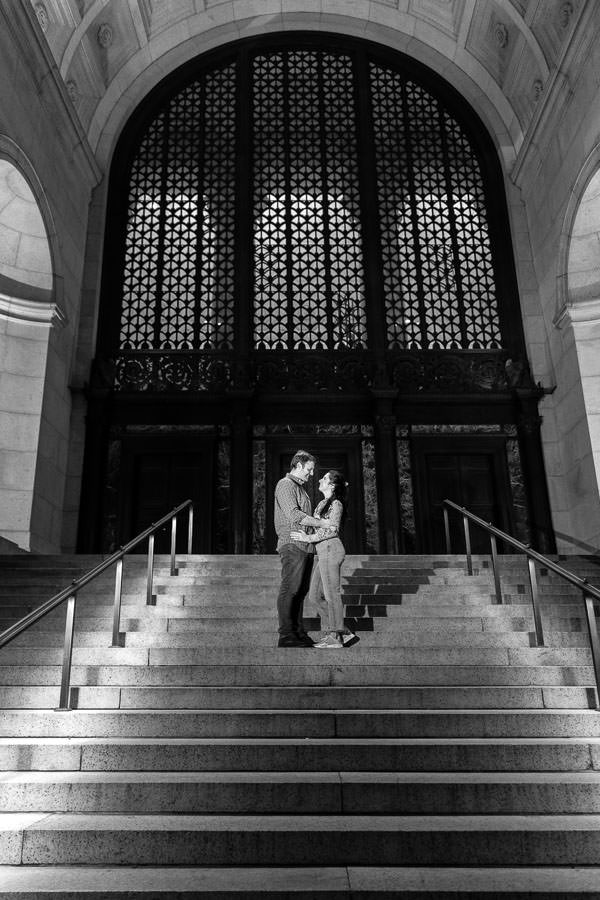 man and girl stand on steps of museum of natural history during night time engagement session