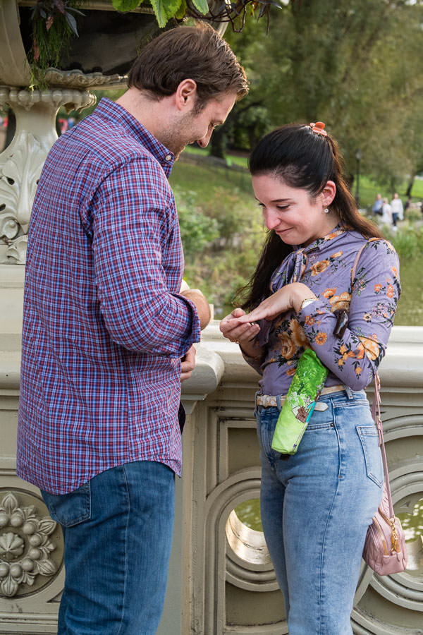 man putting engagement ring on his girlfriends finger during marriage proposal on bow bridge in new york city