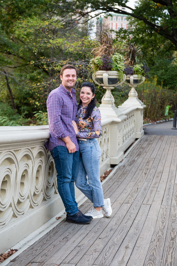 engagement session on bow bridge in central park with man and girl standing and smiling together