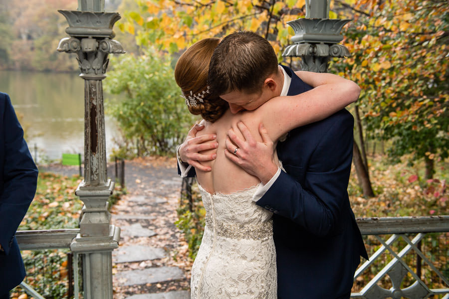 bride and groom hold each other with fall foliage in the background during their central park wedding at ladies pavilion
