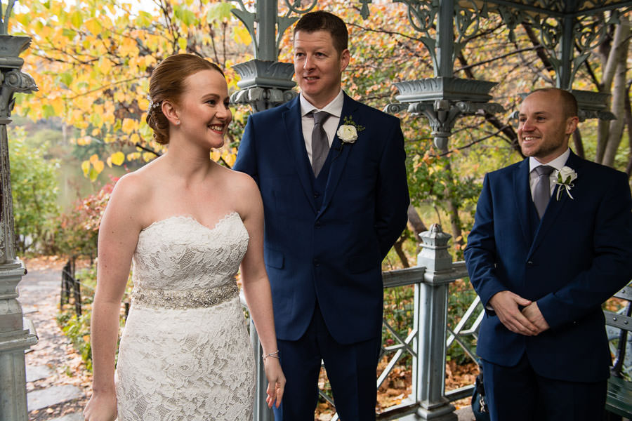 bride and groom look at their guests with best man standing on the side and smiling