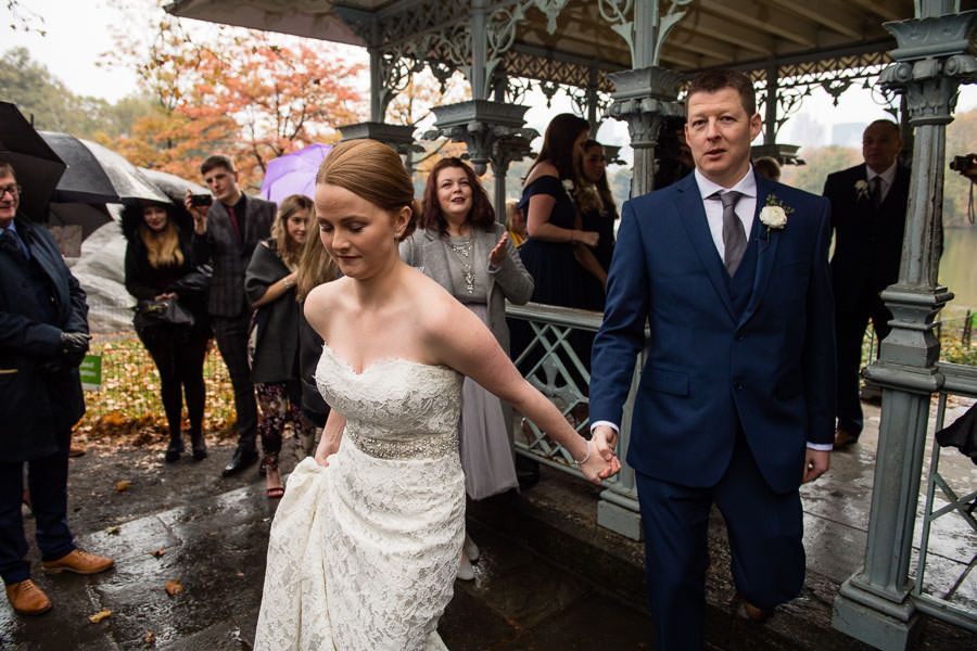 bride and groom hold hands as they exit the ladies pavilion after their wedding and walk out to their guests