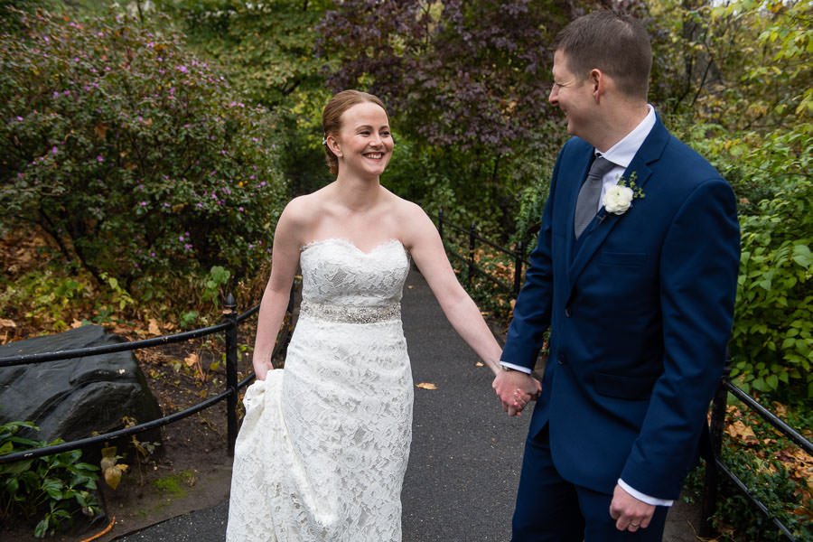 bride and groom hold hands and smile at each other in central park