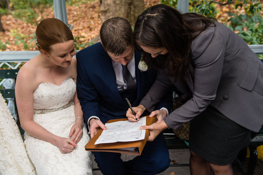 bride and groom sign their marriage certificate in ladies pavilion in central park with their officiant