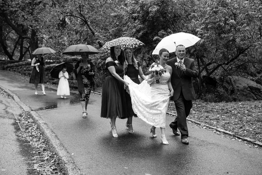 bride and her father walk under and umbrella with bridesmaids holding her bridal dress in central park in NYC