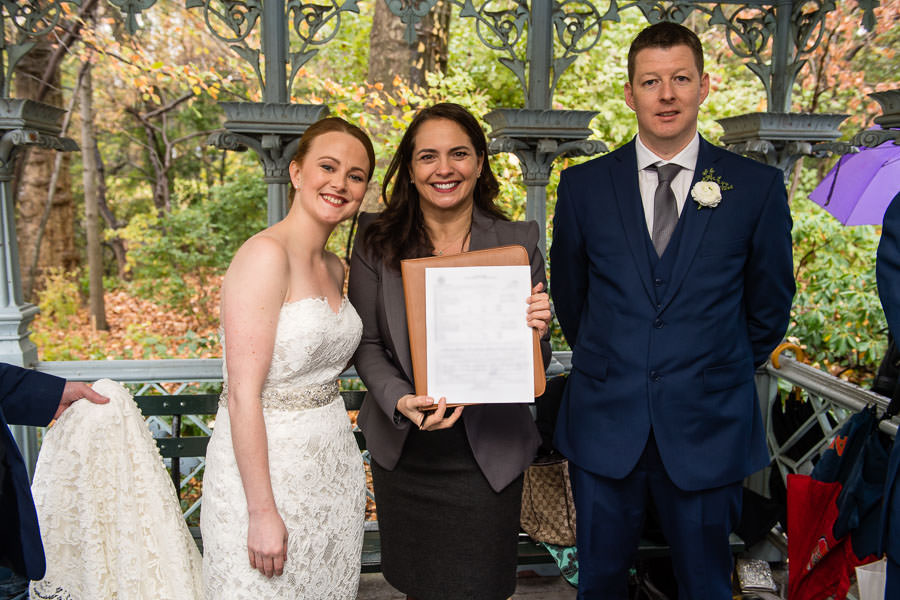 wedding couple stands with their officiant after signing marriage license in central park