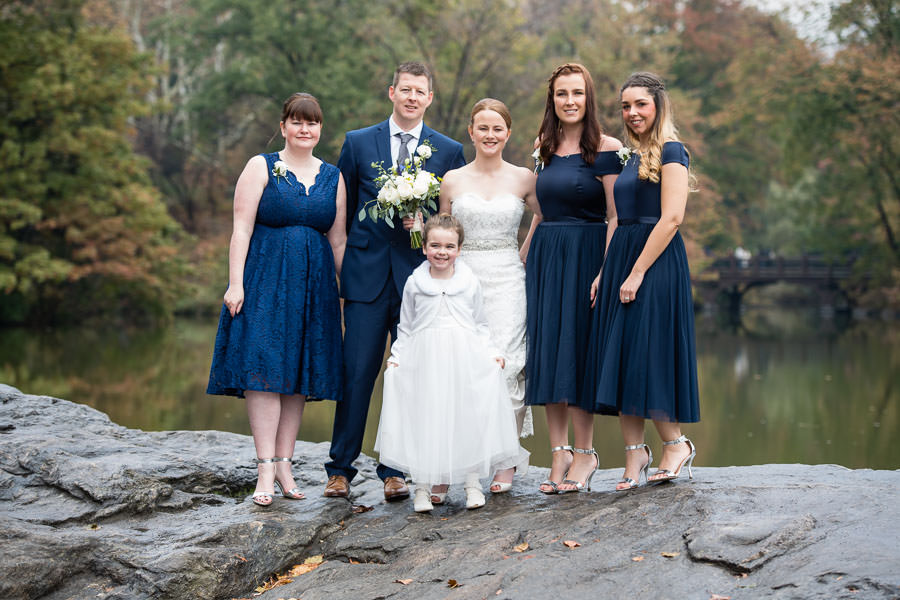 bride and groom with their bridal party in central park and little girl