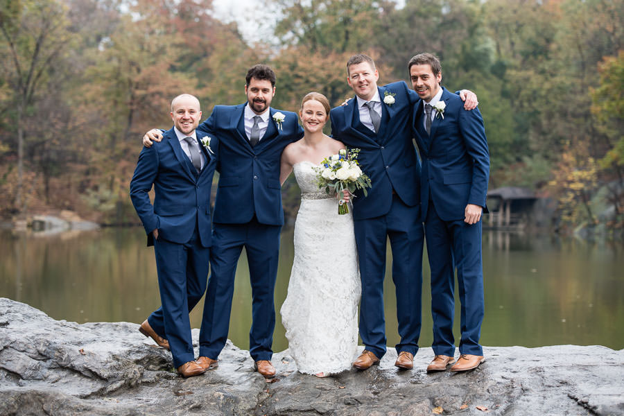 bride and groom stand with groomsmen for group photo with lake in background