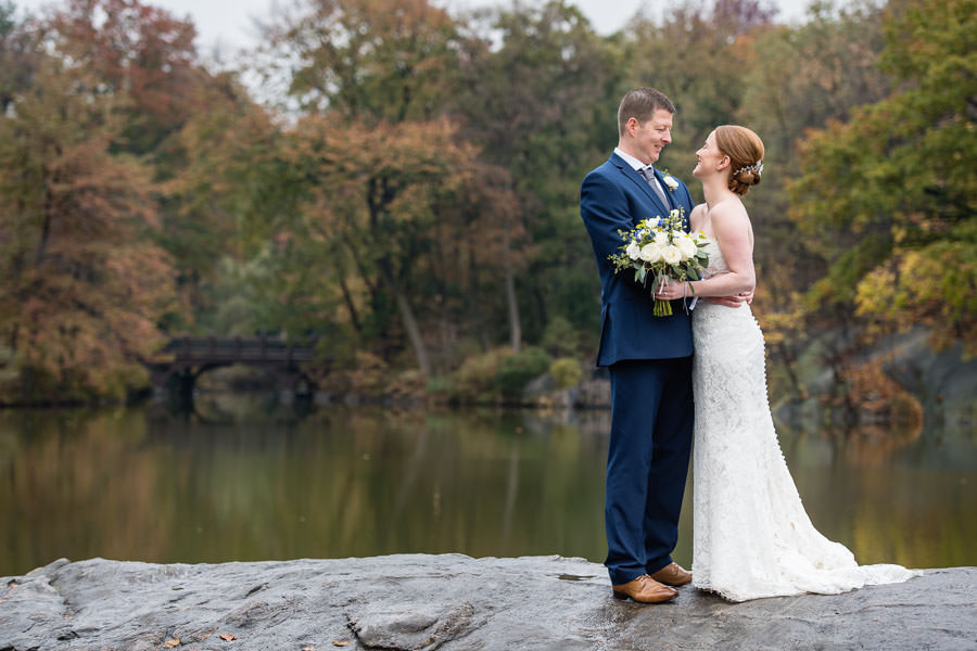 bride and groom pose for photo with fall foliage and lake in the background for their autumn wedding in central park