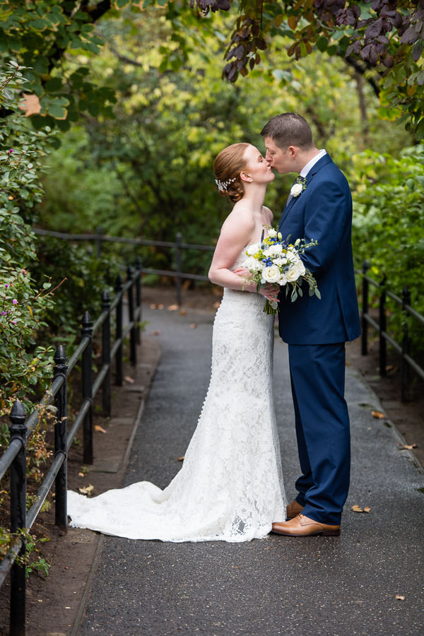 bride and groom kiss while standing in a path in central park