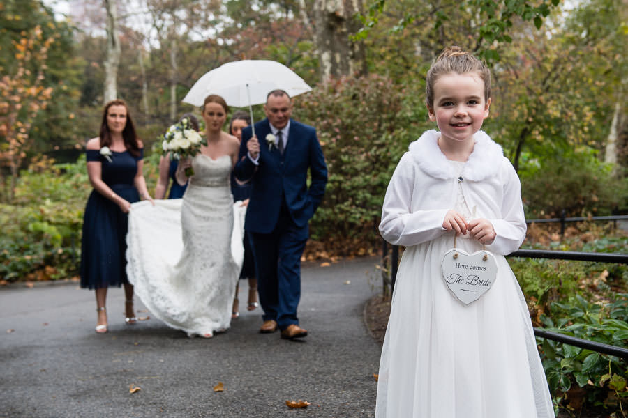 little girl holds sign that says here comes the bride with bride and her father and bridal party walking towards ladies pavilion for their elopement in central park