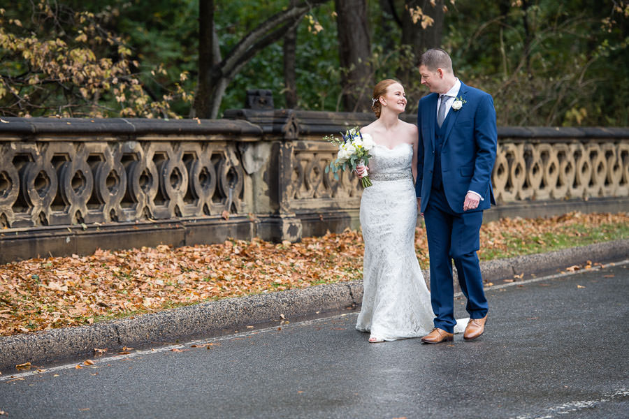 bride and groom walking along street in central park with orange leaves and fence in the background