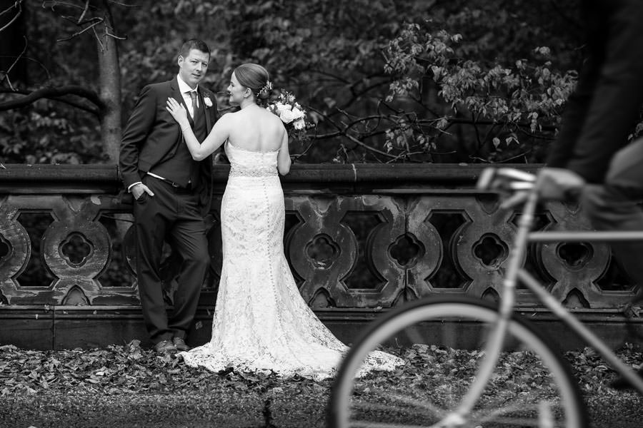 bride and groom pose for photo as bicyclist passes by on the side in central park