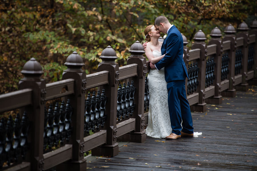 bride and groom are happy and in love with each other as they stand on brown bridge in central park