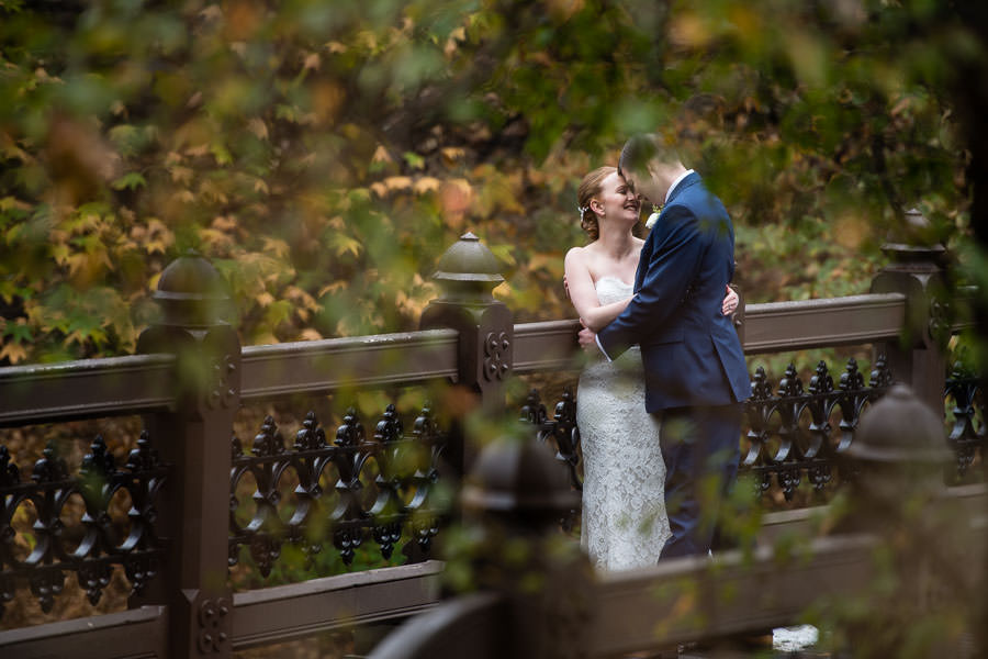 bride and groom smile at each other as they stand on bridge in central park and photo is taken creatively through the leaves of a tree during the fall season in NYC
