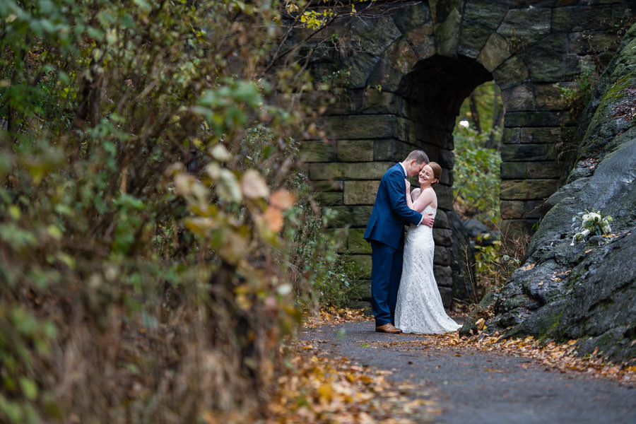 groom makes bride laugh during wedding in central park with fall foliage