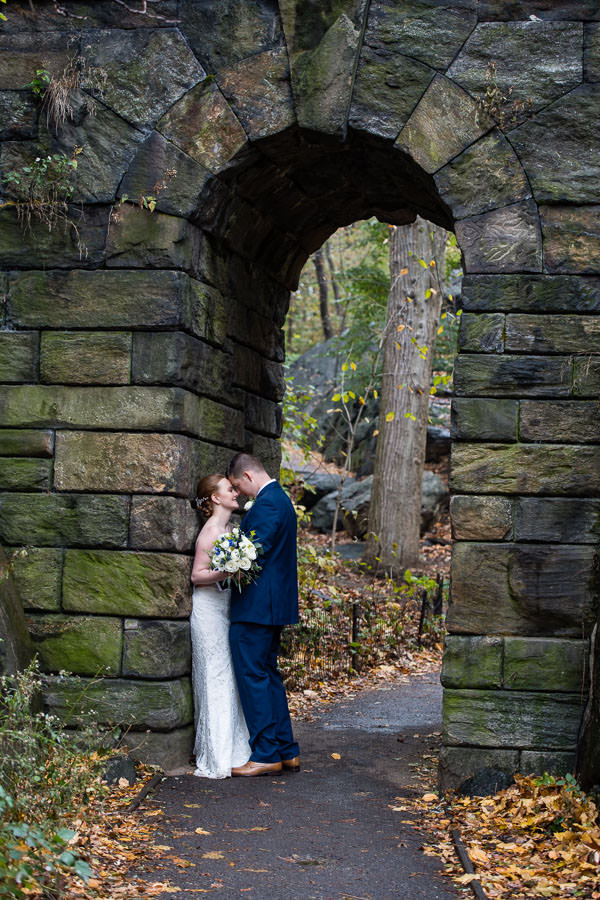 bride and groom pose under tunnel entrance in central park for their fall wedding