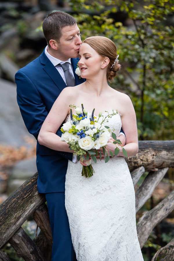 groom kisses his bride's forehead in central park on a little bridge