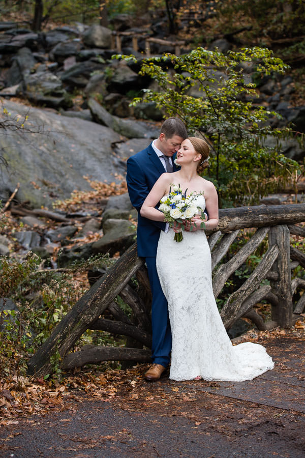 bride and groom pose for photo in central park in the fall with rocks in the background