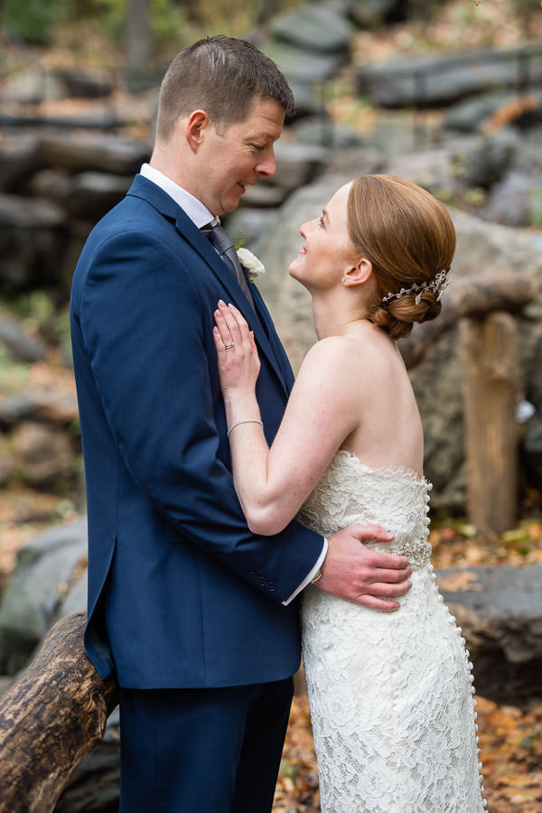 bride and groom look at each other while standing on a brown wooden bridge in central park with fall foliage in the background