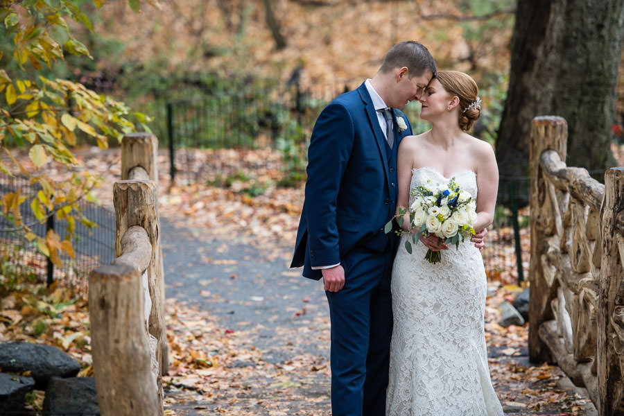 bride and groom stand on wooden bridge in central park