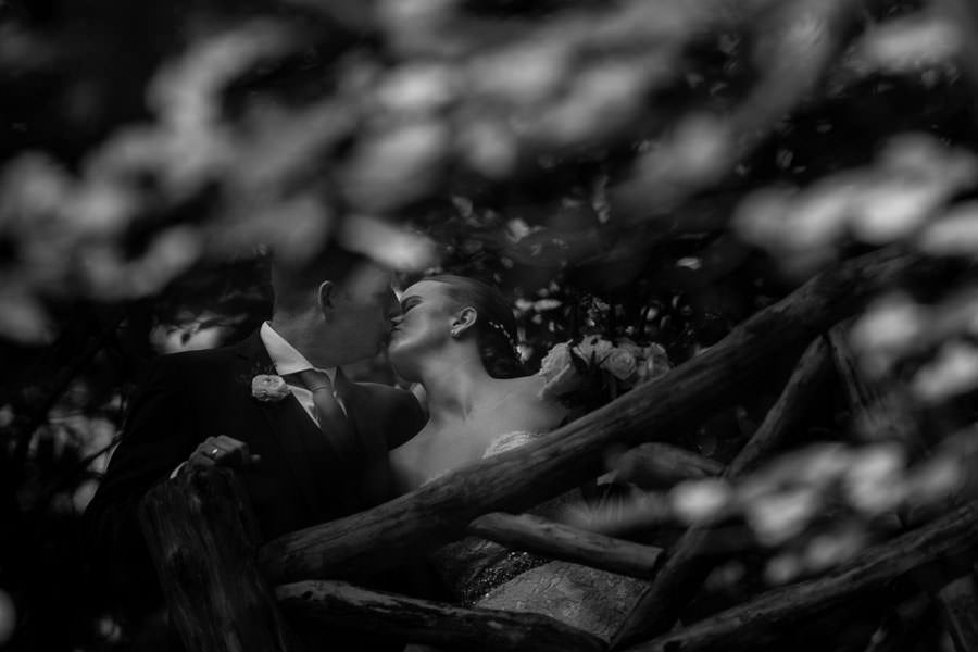 reflection of bride and groom kissing in a pond in central park