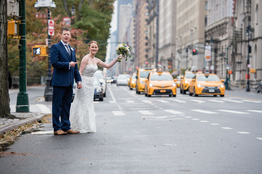 bride and groom try to catch a yellow cab in nyc