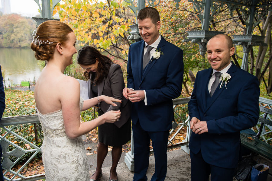 groom prepares to put ring on his bride during elopement in central park in the fall