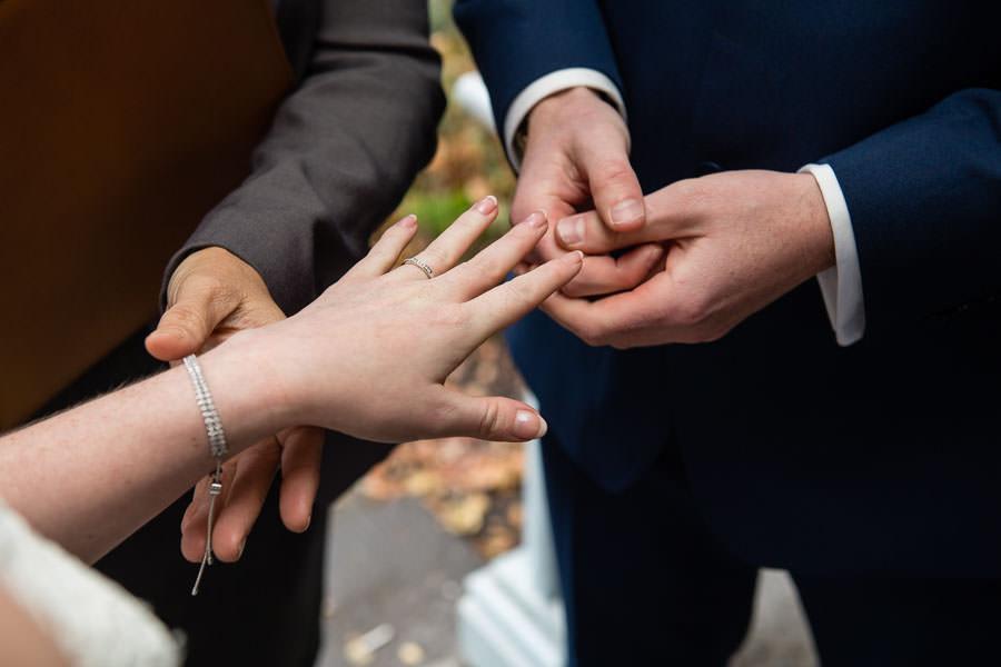 bride and groom exchange wedding rings under ladies pavilion in central park