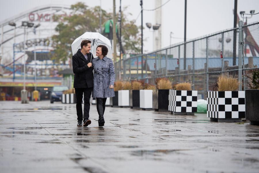 couple walks under clear umbrella in the rain by Luna Park in Brooklyn