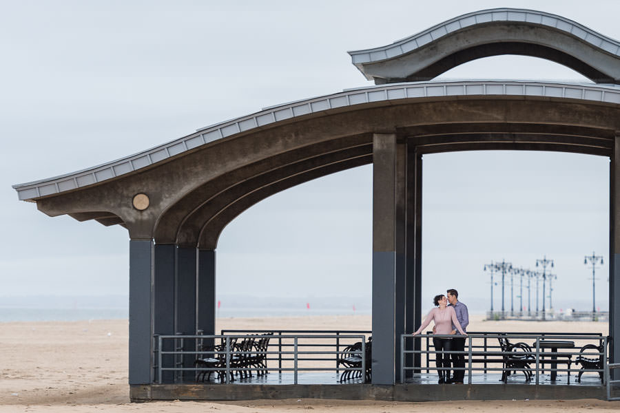 guy and girl standing under roof at the beach in coney island