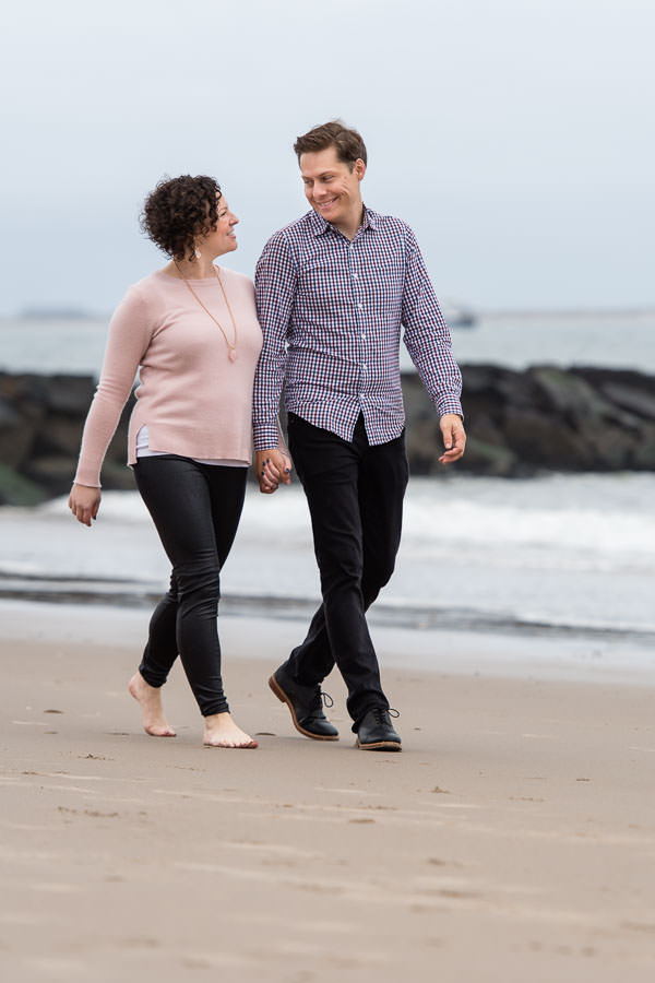 couple holding hands and walking on the beach by the shore with rocks and the ocean in the background